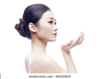 studio portrait of a young and beautiful asian model, side view, isolated on white background.