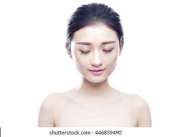 studio portrait of a young and beautiful asian woman, eyes closed, isolated on white background.