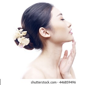 studio portrait of a young and beautiful asian woman, eyes closed, side view, isolated on white background.