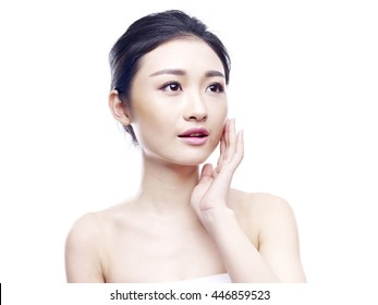 studio portrait of a young and beautiful asian woman, hand on chin, looking up, isolated on white background.