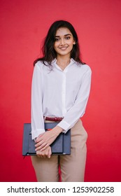 Studio portrait of a young, beautiful and attractive Indian Asian female student holding her laptop and a notebook. She is dressed in corporate casual with a white shirt and khaki pants.