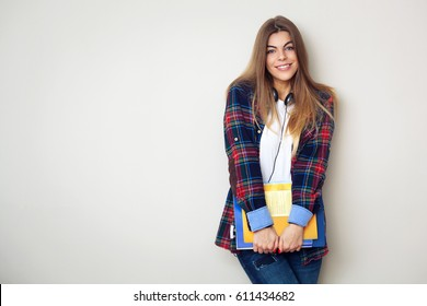 Studio portrait of young beautiful female student with books standing against wall.
