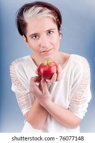 Studio portrait of young beautiful model holding red apple