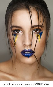 Studio portrait of young beautiful woman with creative colorful  makeup with blue and yellow drops.
