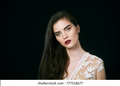 Studio portrait of young beautiful woman with long hair on dark background