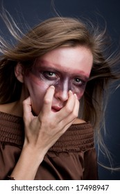 Studio portrait of a young blond woman with aggressive make-up