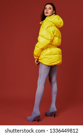 Studio portrait of young brunette woman in yellow down jacket and grey blue panty hoses or stockings. Studio shot