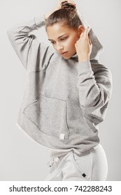 Studio portrait of a young Caucasian girl in a gray sweatshirt. A beautiful girl puts a hood on her head. Gray studio background.