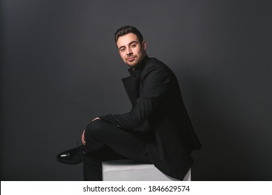Studio portrait of a young caucasian man in a black blazer, looking at the camera, sitting against plain studio background