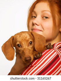 Studio portrait of a young charming woman holding a dachshund