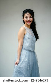A studio portrait of a young Chinese Asian (Singaporean) woman in a fancy blue dress against a white backdrop. She is smiling happily as she poses for her head shot.