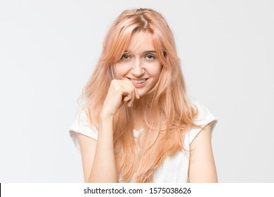 Studio portrait of young cute attractive blonde girl in white t-shirt. Woman raised hand to her lips, look at camera and sexy smile with teeth. Good-looking cheerful female. Youth and beauty concept.
