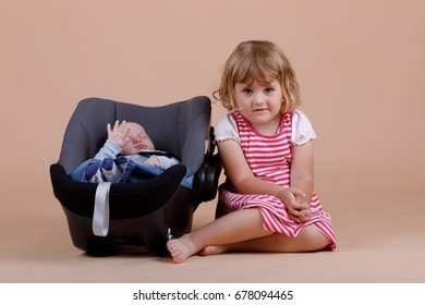 studio portrait of young cute baby girl with infant brother on beige background