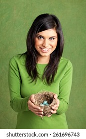 Studio portrait of a young east indian woman holding a birds nest with blue eggs in it.