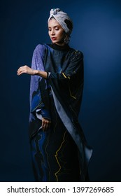 Studio portrait of a young, elegant, tall and slim Middle Eastern Muslim woman wearing traditional clothing for Eid. She is in a flowing dark blue dress and matching turban (hijab head scarf).