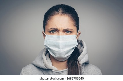 Studio portrait of young frown woman wearing a face mask, looking at camera, close up on gray background. Coronavirus pandemic, dust allergy, protection against virus