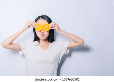 Studio portrait of young funny girl holding two orange slices on eyes on white background and kissing lips. Fresh fruits and healthy diet concept. Free copy space provided