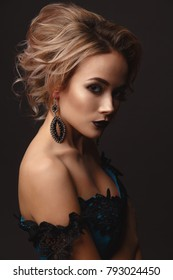 Studio Portrait of a young gentle sexy model girl with stylish makeup on a dark background