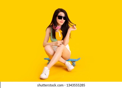 studio portrait of young girl in sunglasses with orange cocktail sitting on skateboard, image on a yellow background