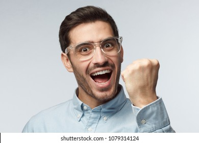 Studio portrait of young handsome European man pictured isolated on gray background with transparent safety glasses showing fist with positive face expression as if having achieved his goal
