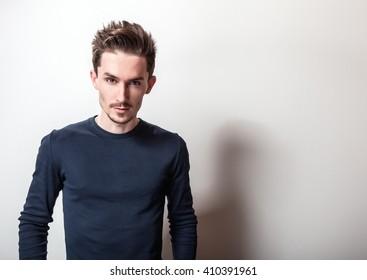 Studio portrait of young handsome man in stylish dark blue t-shirt.