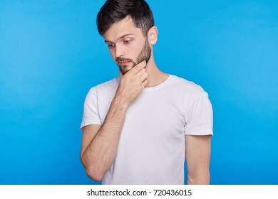 Studio portrait of young handsome man having concentrated thoughtful expression, frowning, keeping hand on his chin as if trying to remember something or making decision on blue wall background.
