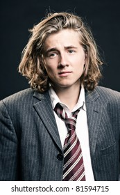 Studio portrait of young hip cool business man with long blond hair on black background.