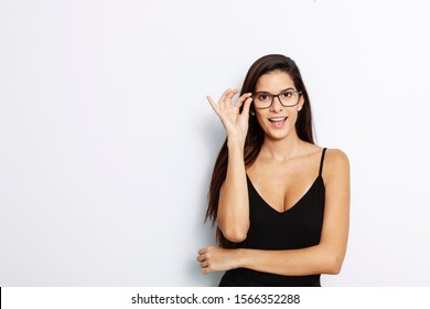 studio portrait of a young Latina with long hair, wearing a black tank top, lsmiling through her black framed glasses, in front of white background,
