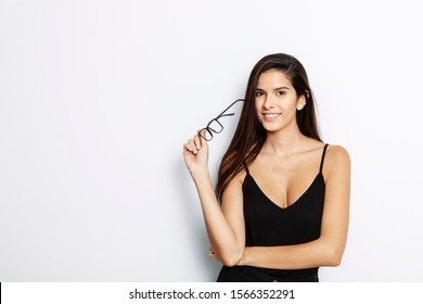 studio portrait of a young Latina with long hair, wearing a black tank top, holding her black framed glasses in her hand, in front of white background,