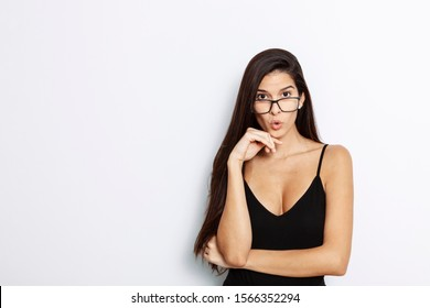studio portrait of a young Latina with long hair, wearing a black tank top, looking astonished over her black framed glasses, in front of white background,