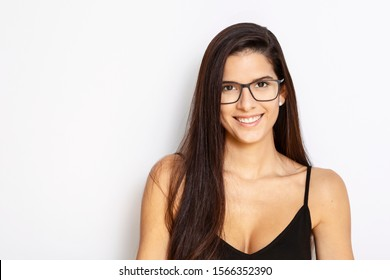 studio portrait of a young Latina with long hair, wearing a black tank top and black framed glasses, with white background, smiling
