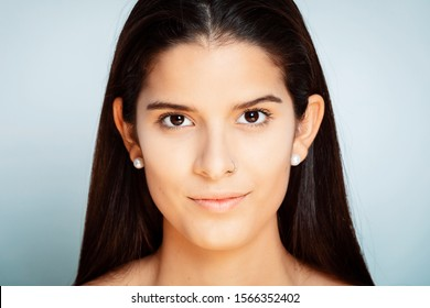 studio portrait of a young Latina with long hair, close to the camera, with white background,