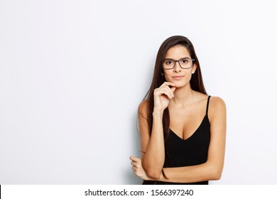 studio portrait of a young Latina with long hair, wearing a black tank top and black framed glasses, with white background,