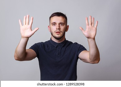 "Studio portrait of a young man keep hands up before him with the expression ""give up"". The concept of harmony, humility, protest, humorous mood."