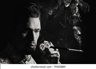 Studio portrait of a young man smoking a cigarette on a black background