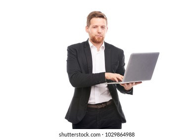 Studio portrait of young manager in suit holding open laptop