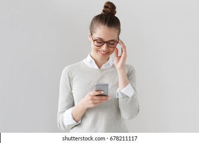 Studio portrait of young naturally looking woman standing isolated against grey background holding cellphone in one hand and touching temple of eyeglasses with other one, and looking at screen.