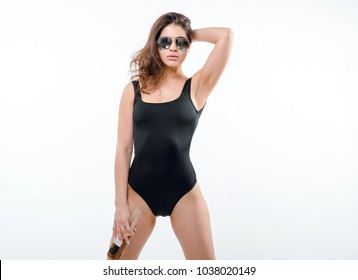 Studio portrait of young pretty sexy woman with beer bottle, Model posing in black bodysuit and sunglasses, fashion and style concept