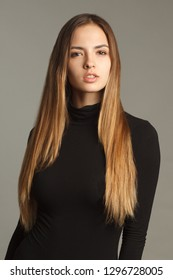 studio portrait of young pretty woman with long beautiful hair on gray background