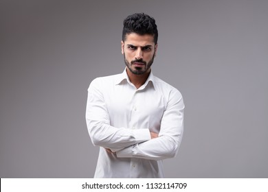 Studio portrait of young serious bearded man in white shirt standing with arms crossed