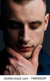 Studio portrait of young sexy man in black shirt, holding hands in chin, looking down with humility and meditation. Body language concept. Wrist Watch.