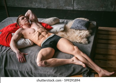 studio portrait young sexy men bodybuilder athlete, with a bare torso, lies on a bed in pillows in underwear