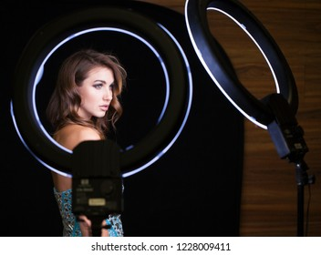 Studio portrait young woman in blue dress with ring flash effect. Round LED Circle Lamp