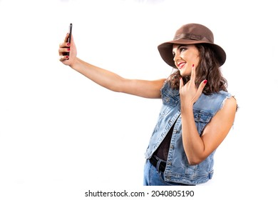Studio portrait of a young woman with a brown hat and a jeans outfit taking a selfie. She stretches her left arm to take the picture while she shows the horns gesture with the right hand.