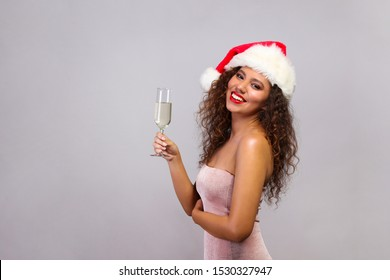 Studio portrait of young woman with dark skin and long curly hair wearing tight sexy dress and santa claus hat, holding glass of champagne. Close up, copy space for text, isolated background.