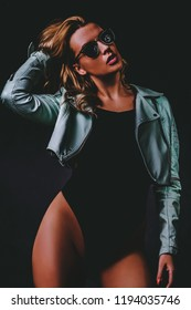 Studio portrait of young woman dressed sunglasses, black bodysuit and mint short leather jacket on dark background.