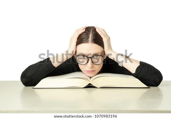 Retrato de estudio de una joven frente a un libro grande sobre la mesa, no tienes ganas de estudiar el concepto