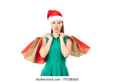 Studio portrait of young woman in Santa hat posing with shopping bags on white background