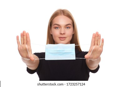 Studio portrait of young woman show a face mask, looking at camera, close up, isolated on white background. Flu epidemic, dust allergy, protection against virus. Blonde woman