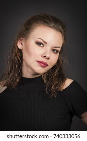 Studio portrait.Girl with makeup and hairstyle on a dark background. Emotions when posing. Studio shot on dark background.